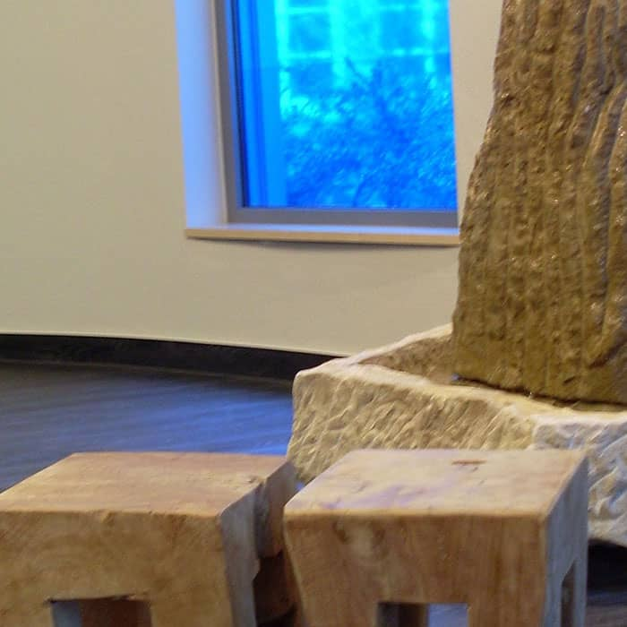 Geschlossener Raum mit Fenster. Holzhocker im Vordergrund, dahinter Steinbrunnen.