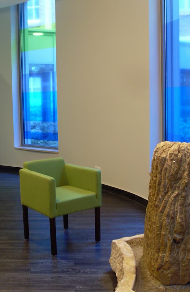 Runde Wand mit Fenstern, davor grüner Sessel und ein Steinbrunnen.