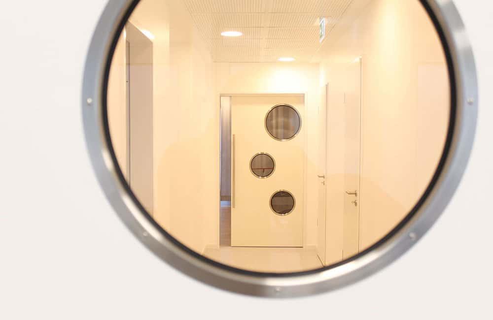 Blick durch rundes Fenster in den Flur und auf eine weitere Tür mit runden Fenstern.