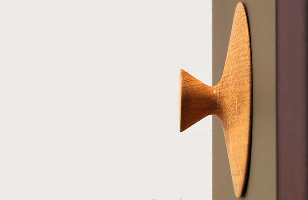Garderobenhaken aus Holz auf dunkler Wand.