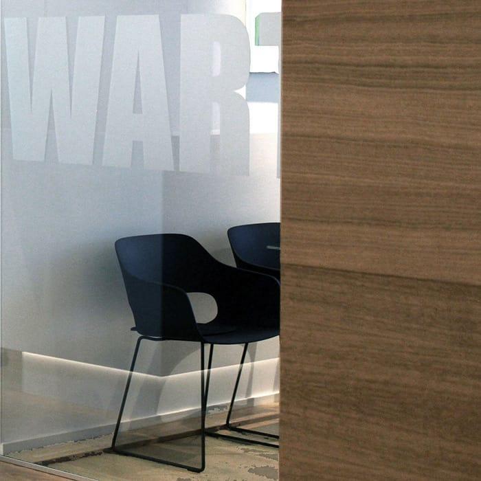 Glasscheibe mit Grafik und dahinter sichtbaren schwarzen Stühlen.