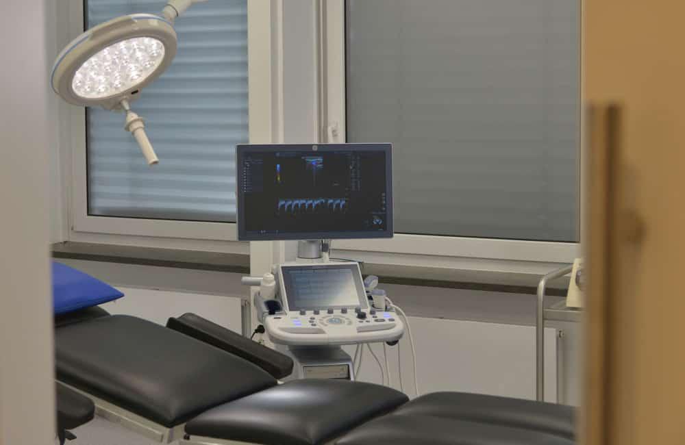 Untersuchungsliege mit Untersuchungsleuchte und Ultraschallgerät mit Monitor.