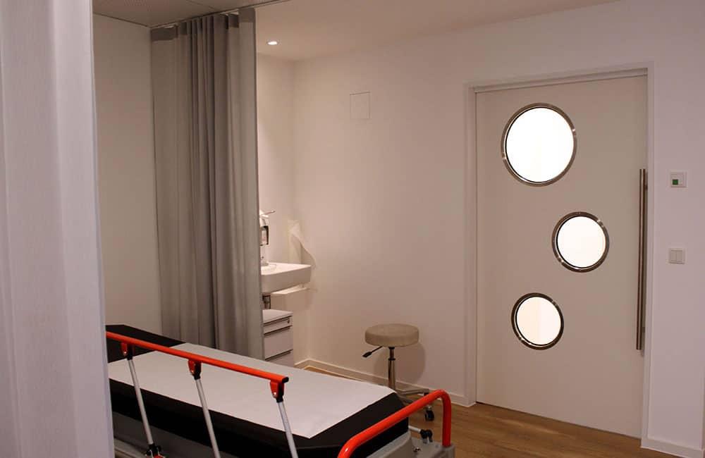 Liege im Op-Bereich mit Vorhängen zum Raum trennen, im Hintergrund weiße Tür mit runden Glasfenstern.