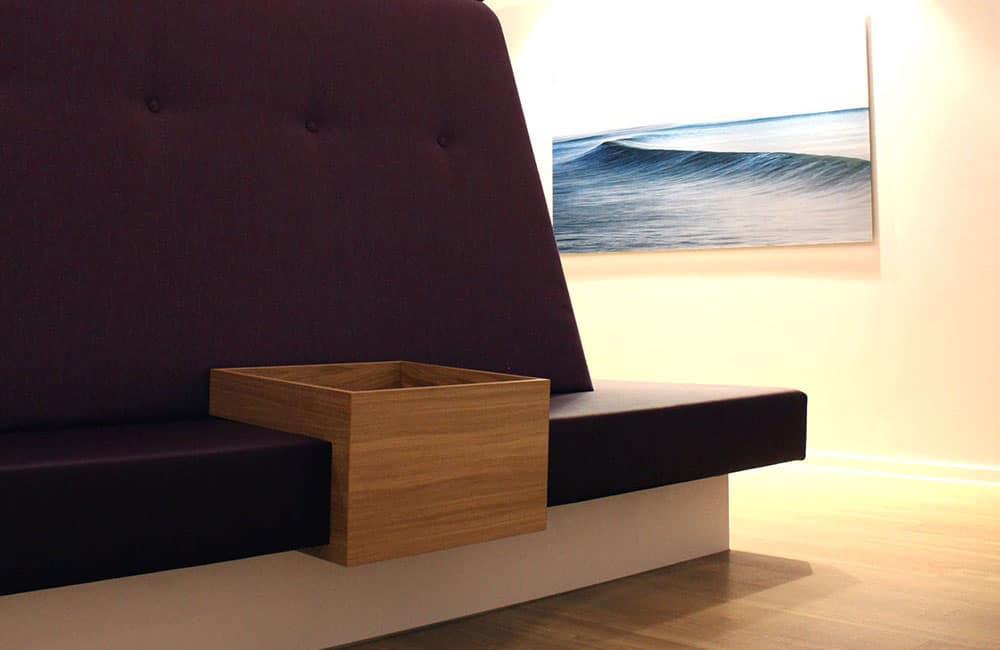 Sitzbank mit integriertem Ablagemöbel. Dahinter akzentuiert beleuchtete Wellenfotografie.