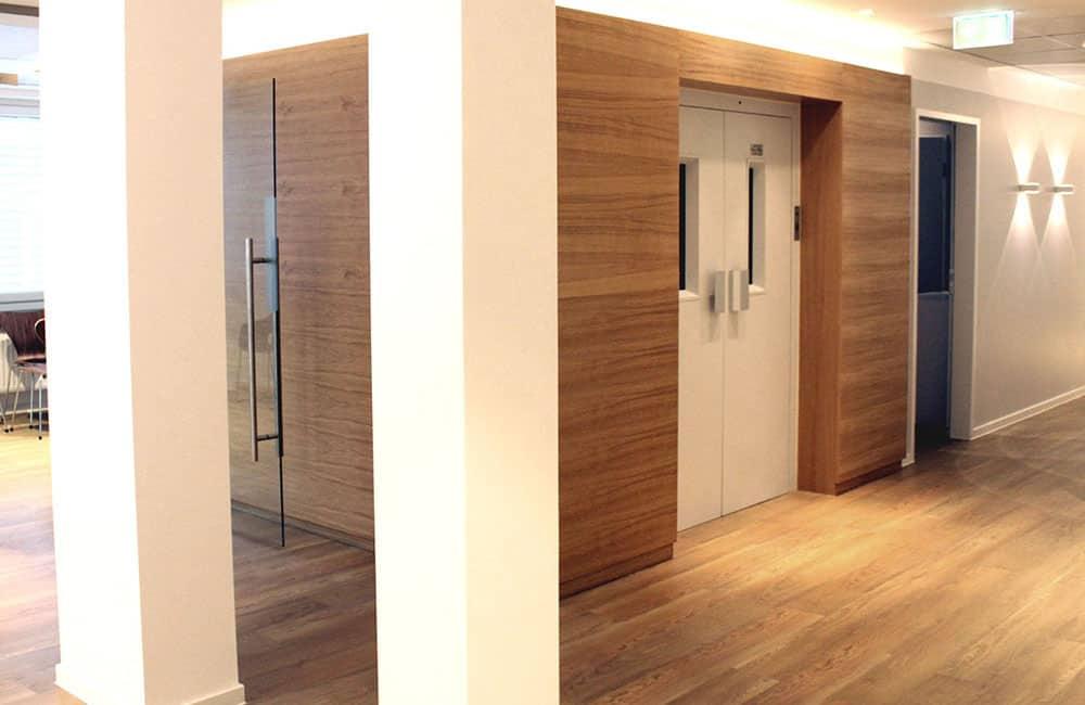Fahrstuhlschacht, in Holzoptik verkleidet und mit indirekter Beleuchtung.