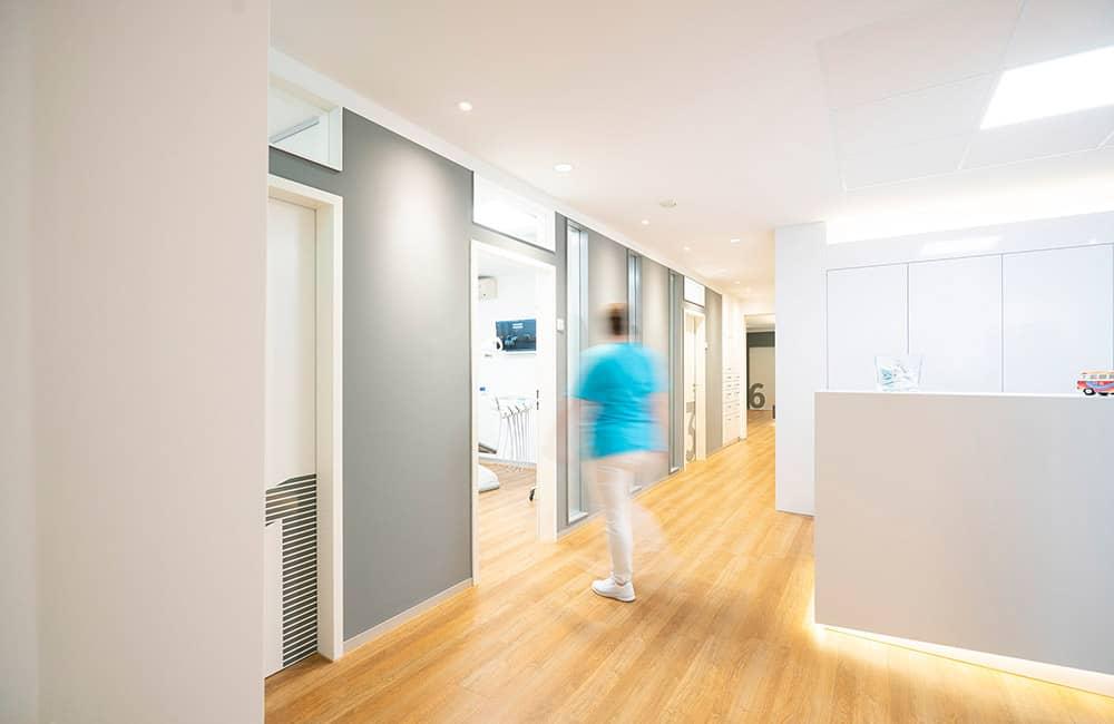 Modernes Praxisdesign aus Hannover: Empfang mit Designtresen und weißem Einbauschrank. Auf der linken Bildseite graue Wand mit Türen zu den Behandlungsräumen.