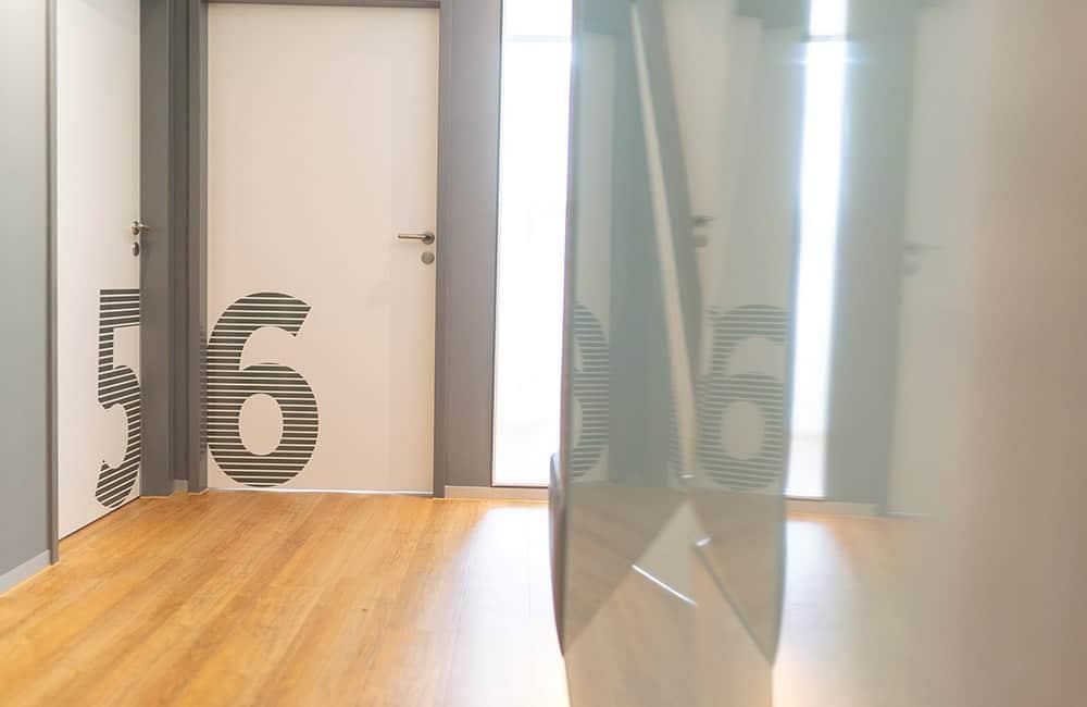 Weiße Türen mit großen grafischen Zahlen. Rechts im Bild Glasscheibe mit Spiegelung des Flures.