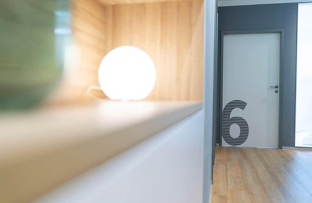 Nahaufnahme eines Einbaumöbels mit runder Leuchte. Dahinter Ausschnitt des Flures mit grauer Wand und weißer Tür.
