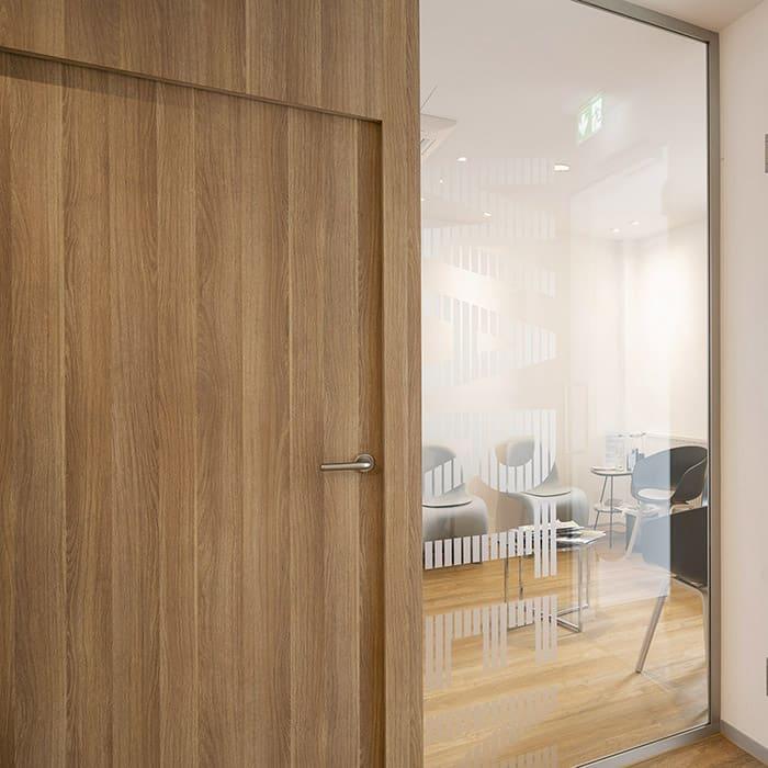 Holztür in Holzwand mit eingebauter Glasscheibe, durch die man in ein Wartebereich blickt.