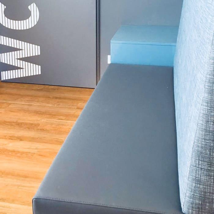 Nahaufnahme der graublau gepolsterten Sitzbank, dahinter liegende graue Wand.