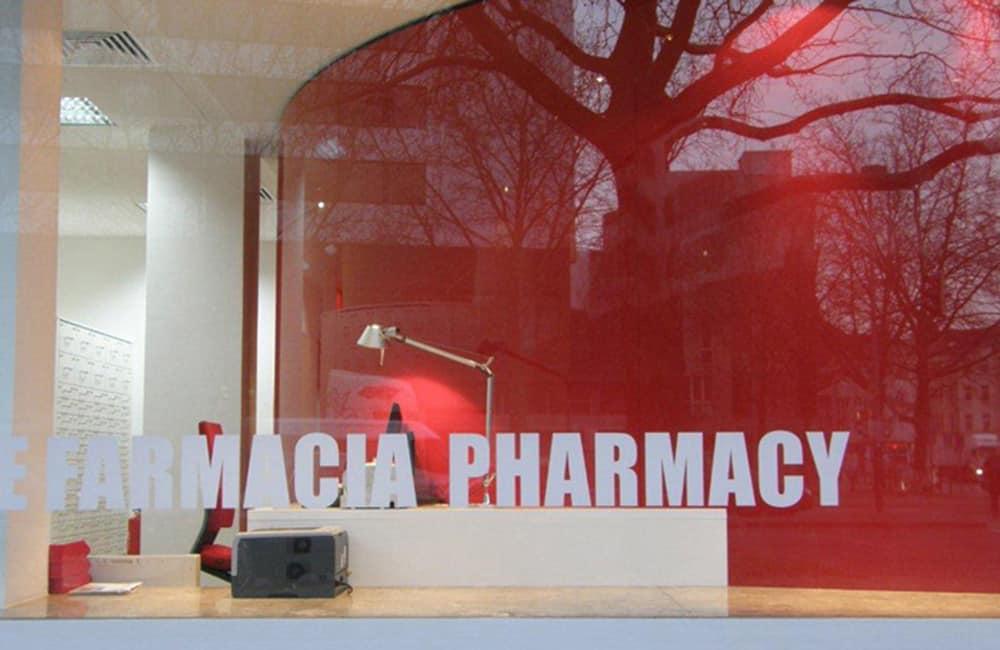 Moderner Ladenbau: Grafische Schrift auf Schaufenster, dahinter runde und knallig rote Wand.