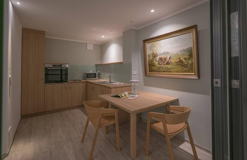 Eine moderne Einbauküche in Holzoptik mit einem kleinen Holztisch und zwei Stühlen.