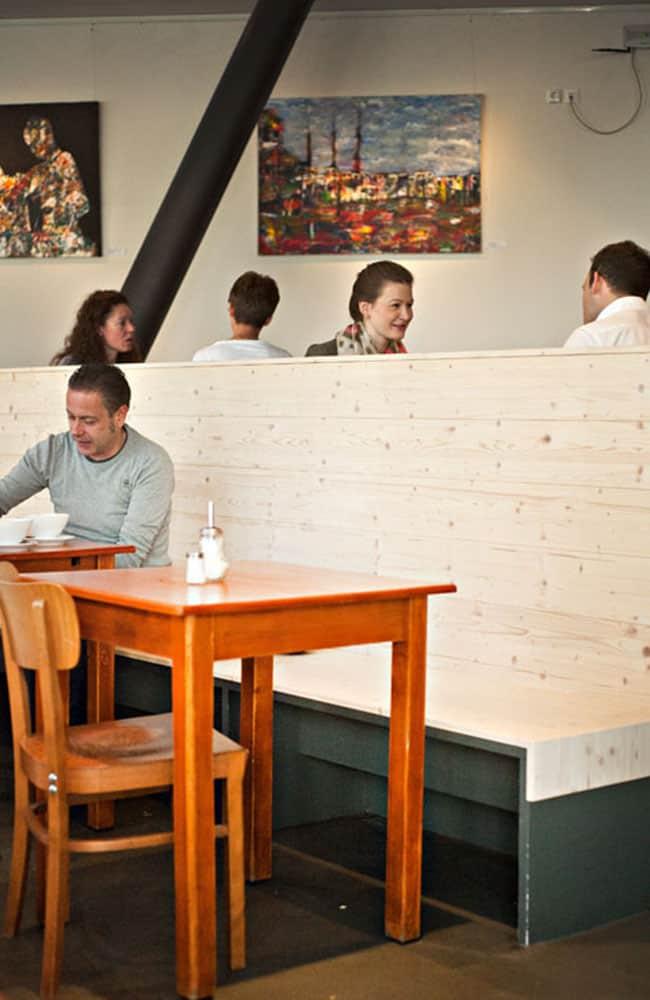 Restaurant mit heller Holzbank und alten Holztischen und Gästen.