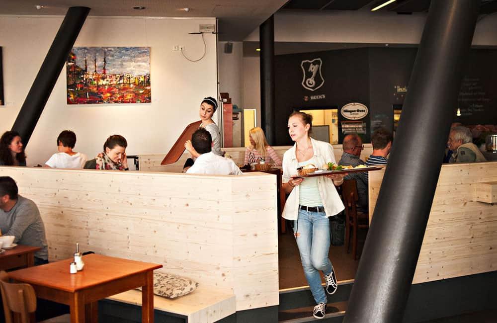 Restaurant mit Holzbank und vielen Gästen und Kellnern.