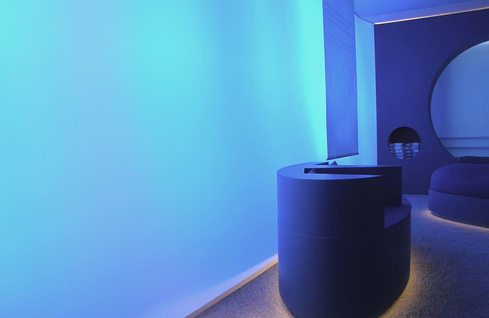 Blau illuminierte Wand und immateriell wirkende Möblierung.