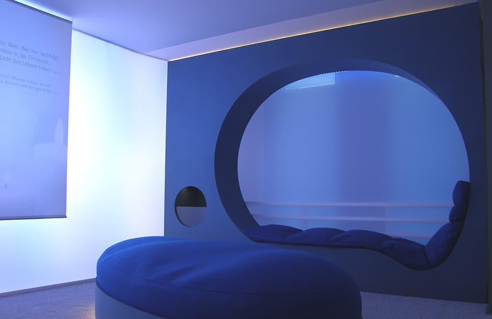 Sitznische eingebaut in blaue Wand mit indirekter Beleuchtung.