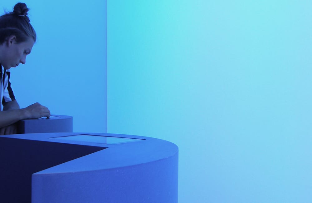Blau illuminierte Wand und immateriell wirkende Möblierung. Mann steht seitliche am linken Bildrand und schaut auf ein Display.