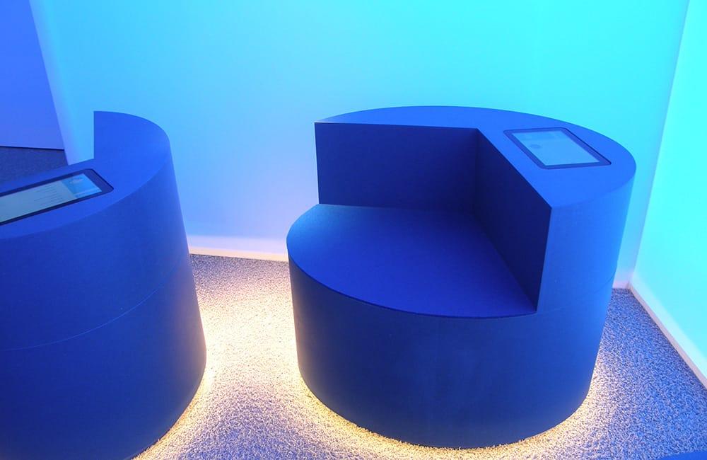Blaues und rundes Sitzmöbel mit eingebautem Display in einem blau illuminierten Raum.