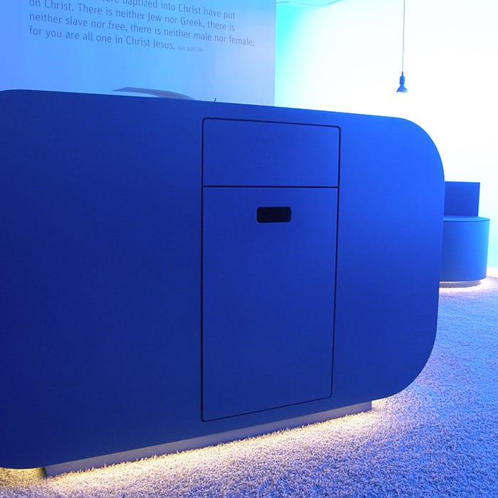 Blaues Sideboard mit abgerundeten Kanten und indirekter Beleuchtung.