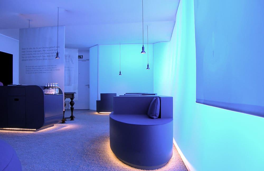 Leuchtende Wände und Möbel mit abgehängten Deckenleuchten.