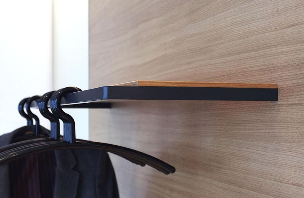 Metallgarderobe mit Ablage und Rückwand aus hellem Holz.