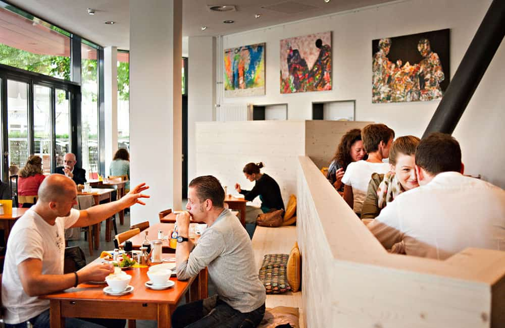 Sitzbank aus hellem Holz bietet vielen Gästen Sitzmöglichkeit. Im Hintergrund hängen Kunstleinwände an den Wänden.