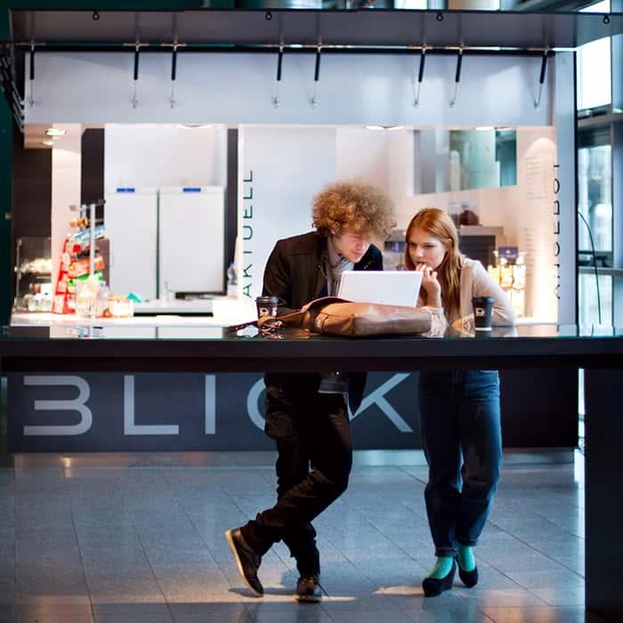 Mann und Frau stehen am Hochtisch und schauen auf einen Laptopbildschirm. Dahinter grauer Verkaufskiosk mit grafischer Schrift.