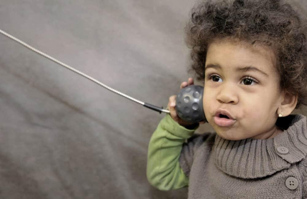 Kind mit Hörer am Ohr. Im Hintergrund grauer Stoff.