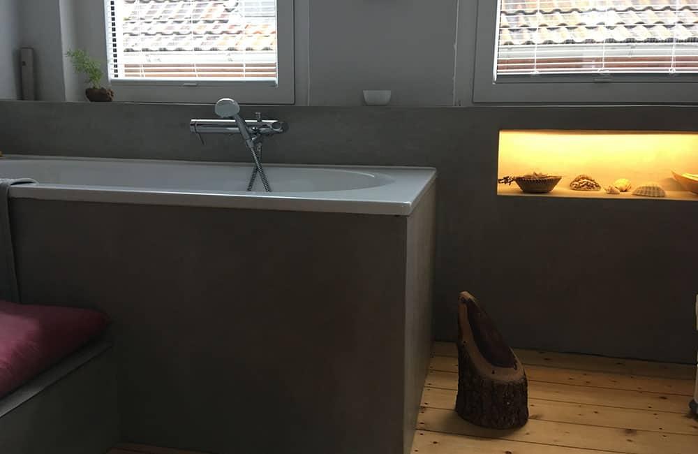 Modernes Badezimmer mit Badewanne und hinterleuchteter Einbaunische in Vorsatzwand.
