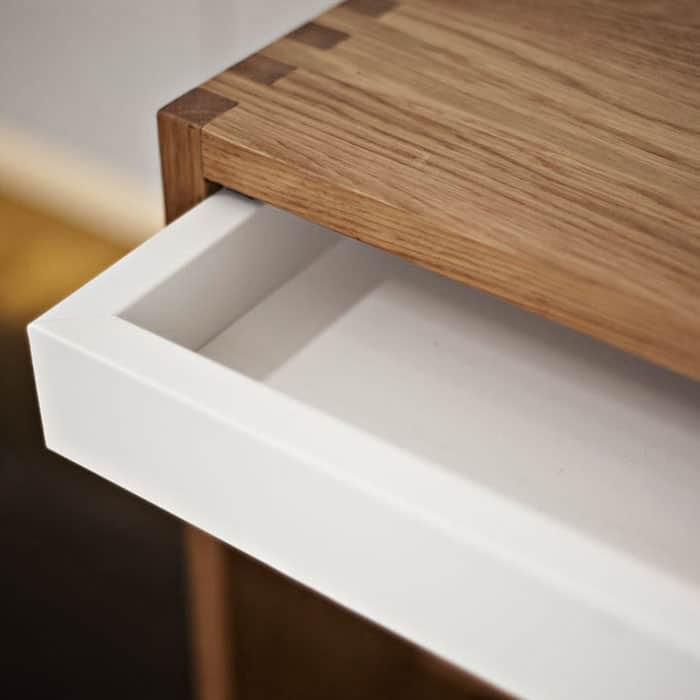 Detailaufnahme eines Holzmöbels mit teils rausgezogener weißer Schublade.