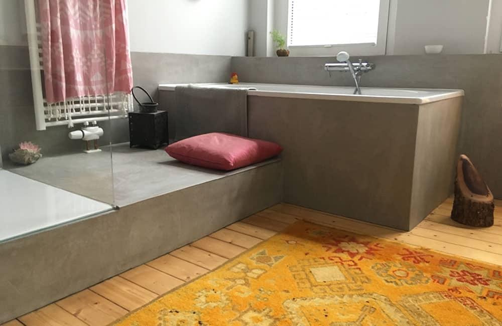 Holzdielenboden mit einem Teppich in einem modernen Badezimmer mit Dusche und Badewanne.