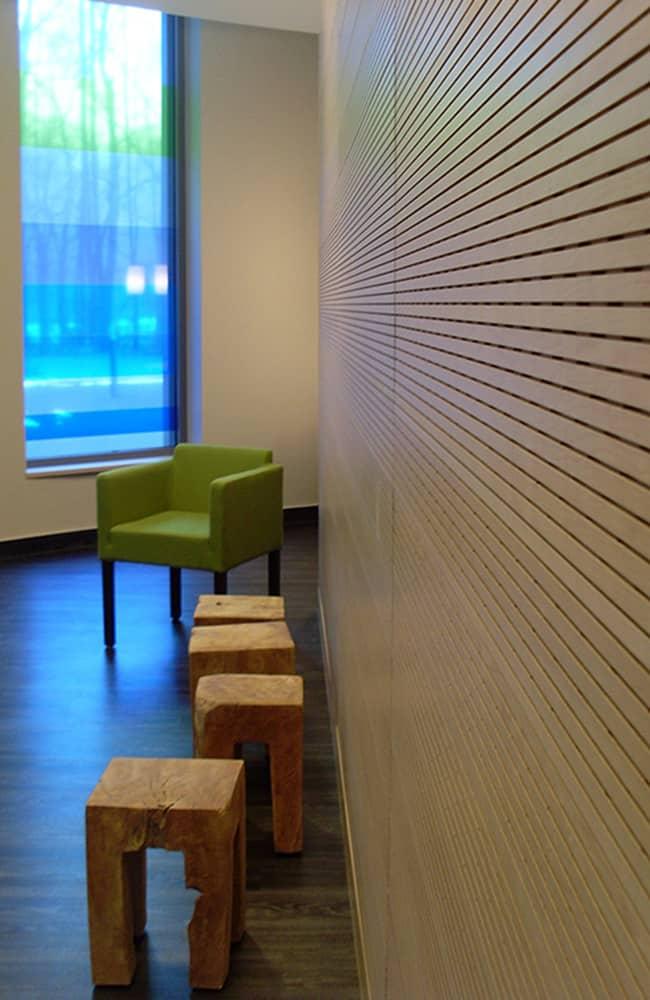 Naturholzhocker und Sessel vor holzverkleideter Wand. Farbiges Fenster aus dem Licht scheint.