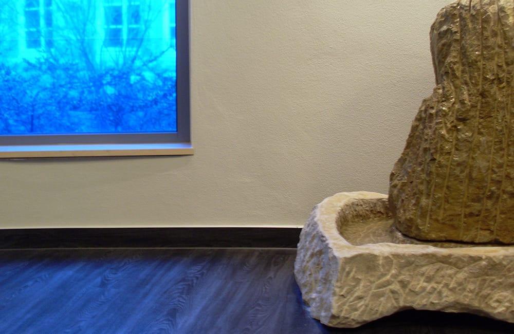 Natursteinbrunnen vor weiß verputzter Wand und daneben einem mit blauer Folie beklebten Fenster.