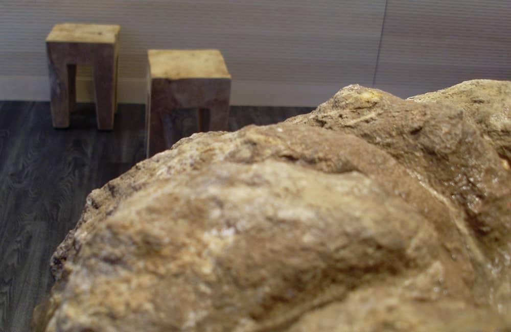Nahaufnahme eines Steins. Im Hintergrund stehen zwei Naturholzhocker auf einem Holzfußboden.