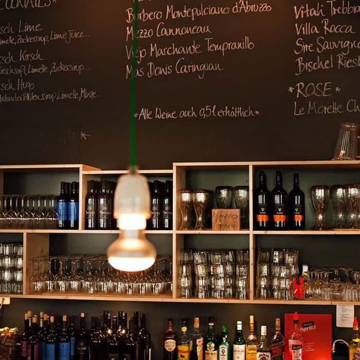 Barregal mit Gläsern und Flaschen, darüber graue Tafelwand mit Getränkeangeboten und eine Hängeleuchte im Vordergrund