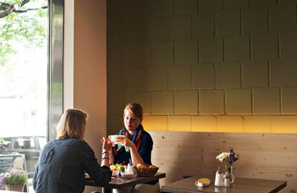 Zwei Frauen sitzen am Tisch auf einer hinter leuchteten Holzbank. Dahinter grüngestrichene Mauerwand.