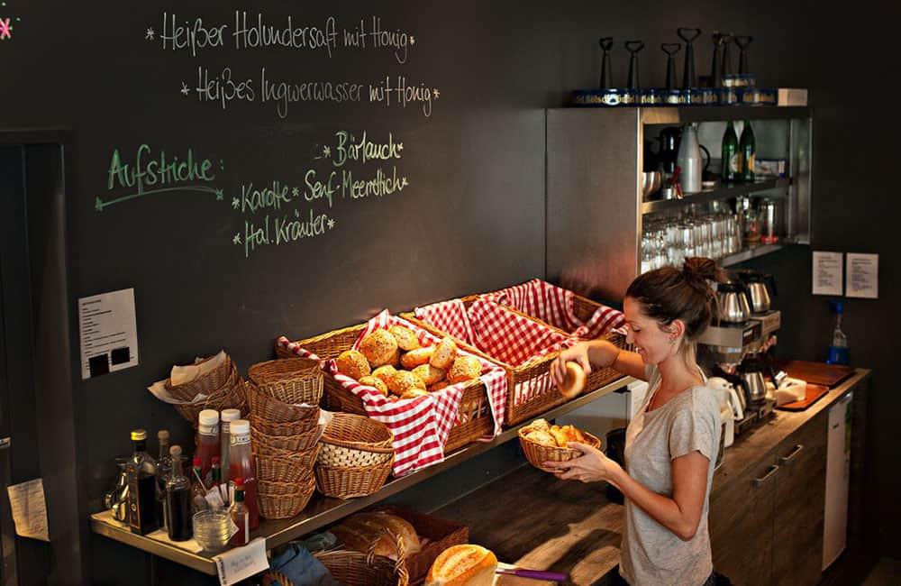 Kellnerin steht an der Arbeitszeile vor Brötchenkörben. Darüber dunkle Tafelwand mit Kreideschrift.