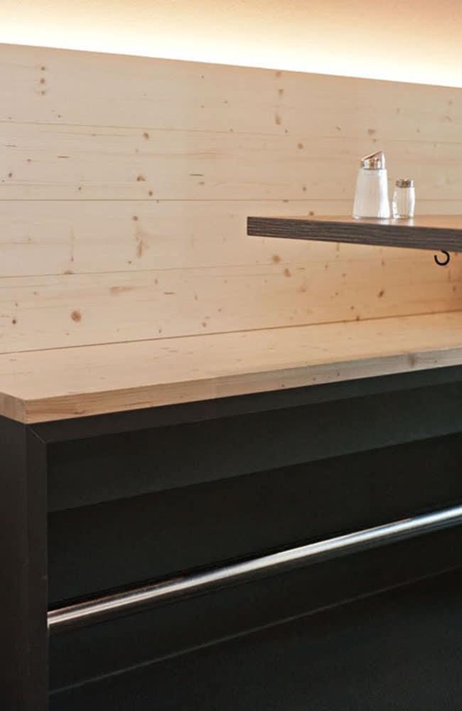 Holzbank mit dunklen Füßen und oben indirekte Beleuchtung an die Wand.