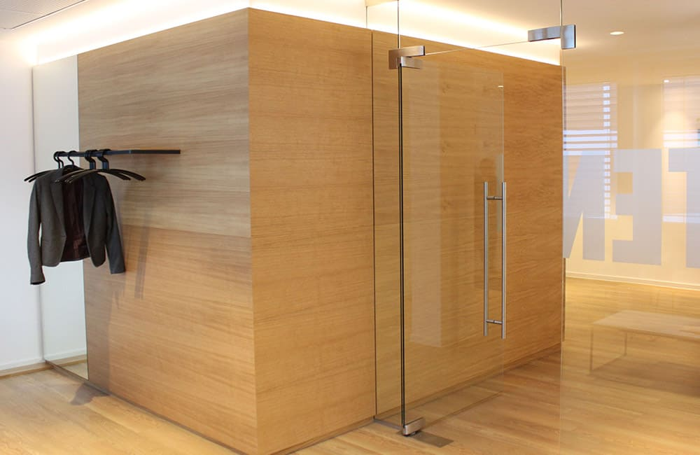 Holzverkleidetes Raumelement mit indirekter Beleuchtung und integrierter Garderobe. Daran anschließend eine Glastrennwand mit Tür.