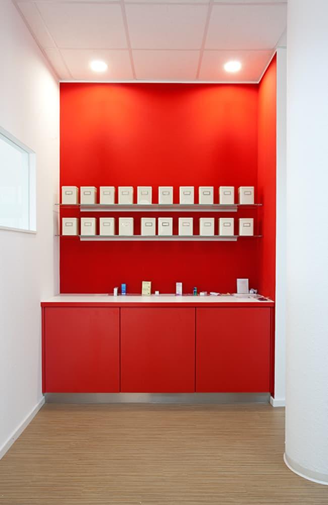 Knallig rote Arbeitsnische mit darüber liegenden Glasböden.