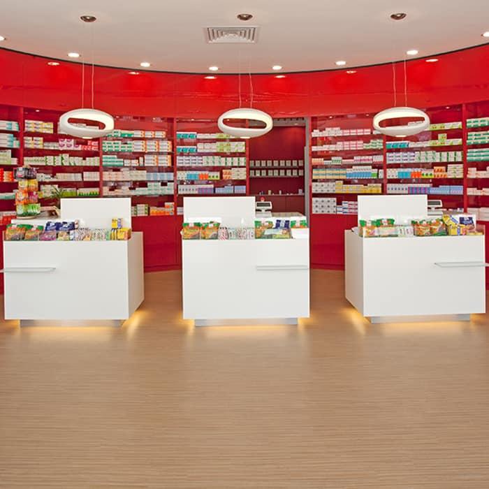 Verkaufstische, indirekt hinterleuchet und mit hängenden Designleuchten. Dahinter rundes Produktregal in knalligem Rot.