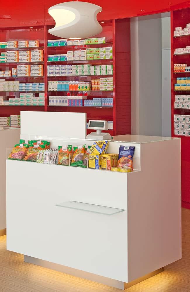 Verkaufstisch mit Produktauslage und Taschenablage. Dahinter rotes Warenregal.