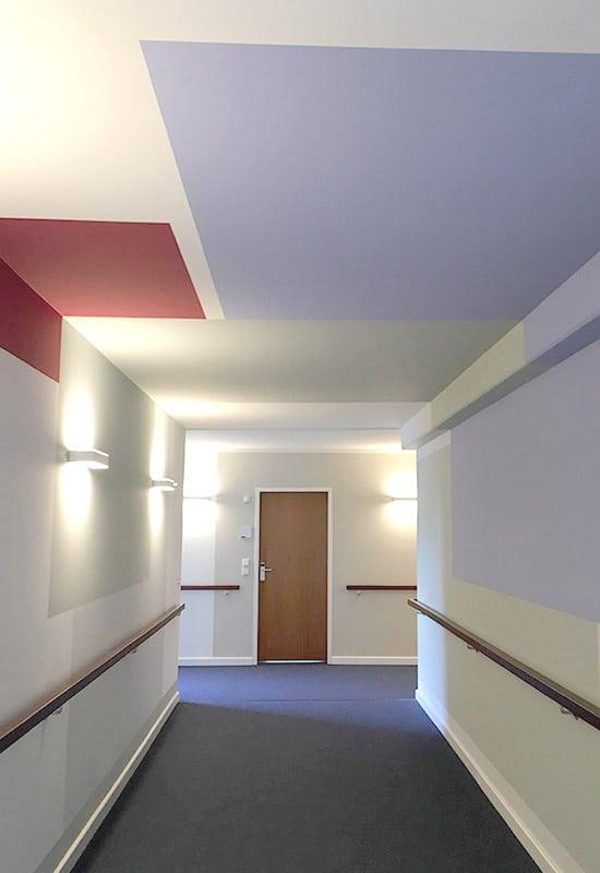 Blick durch einen Flur mit farbigen Flächen an Wand und Decke mit modernen Wandleuchten.