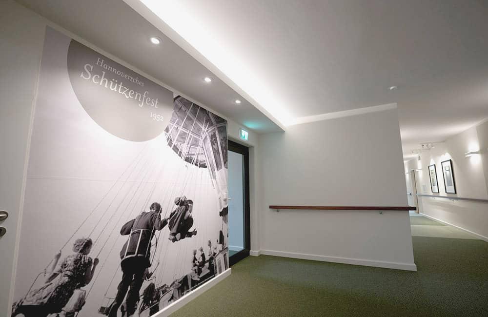 Wand mit einem großformativen Foto, dahinter verläuft ein langer Flur.