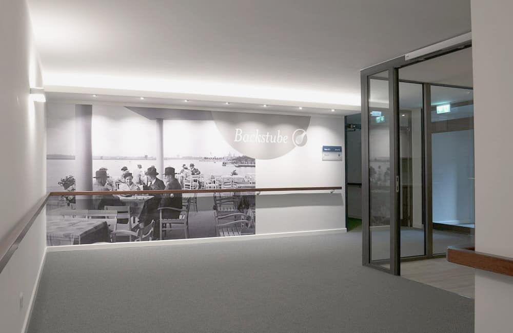 Wand mit einem großformativen Foto, über dem ein Leuchtstreifen verläuft.