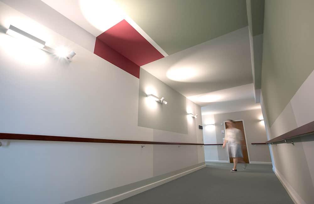 Farbige Flächen an Wand und Decke mit modernen Wandleuchten.