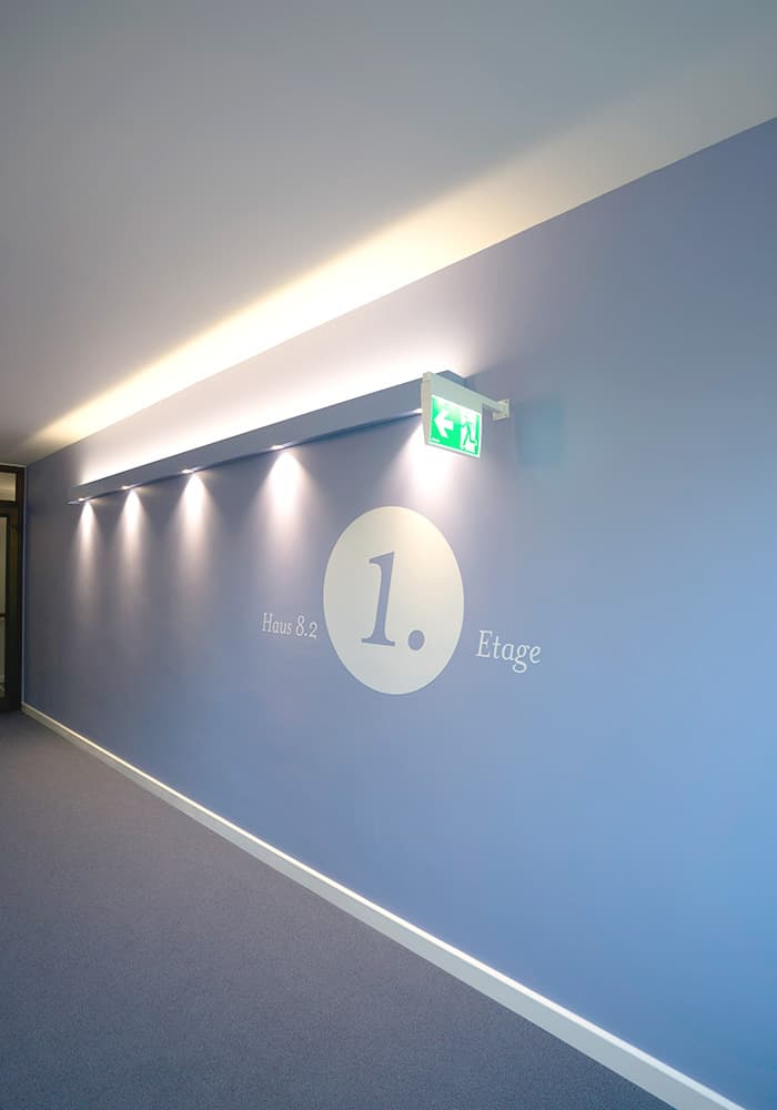 Blaue Wand mit Lichtakzenten und Grafik zur besseren Orientierung.