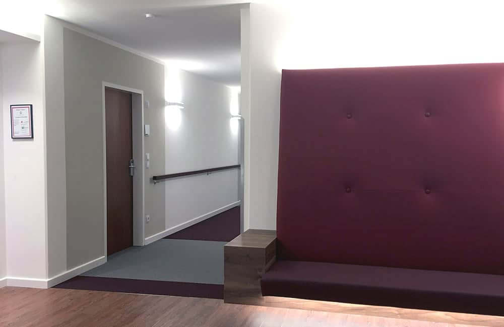 Hinterleuchtete Einbausitzbank an der Wand, daneben Sicht in einen Flur mit farbigen Flächen.